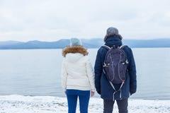 junges Paar wandert auf einem Wintersee lizenzfreie stockfotos