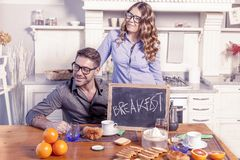 Junges Paar zeigt ein Brett mit Frühstückseinladung Stockfotos