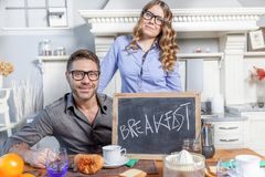 Junges Paar zeigt ein Brett mit Frühstückseinladung Stockfotografie