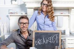 Junges Paar zeigt ein Brett mit Frühstückseinladung Stockfoto