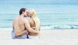 Junges Paare relaxin auf einem Sommerstrand Stockbilder