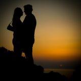 Junges Paarsonnenuntergang silhoutte auf einer Küste während des Feiertags Stockfotografie