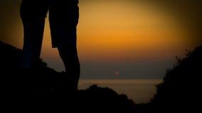 Junges Paarsonnenuntergang silhoutte auf einer Küste während des Feiertags Stockfoto