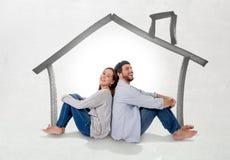 Junges Paarträumen und -darstellung ihr neues Haus im Konzept des wirklichen Zustandes stockbilder