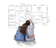 Junges Paarträumen und -darstellung ihr neues Haus im Konzept des wirklichen Zustandes stockfotografie