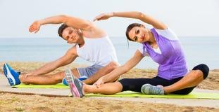 Junges Paartrainingsyoga wirft das Sitzen auf Strand auf Lizenzfreie Stockbilder