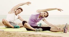 Junges Paartrainingsyoga wirft das Sitzen auf Strand auf Stockfoto