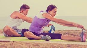 Junges Paartrainingsyoga wirft das Sitzen auf Strand auf Stockfotografie