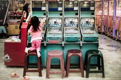 Junges playfulgirl klettert auf einen Stuhl, der versucht, die Spitze der Flipperautomatsäulengangmaschine zu erreichen stockbilder