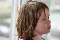 Junges Porträt des kleinen Mädchens, das heraus Fenster schaut Stockfotografie