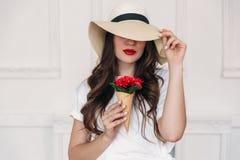 Junges Porträt des Schönheitsstrengen vegetariers, einen Strohhut mit großen Feldern tragend und bedecken ihre Augen, Lippen rot  lizenzfreie stockfotos