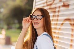 Junges positives attraktives hübsches Mädchen in den stilvollen Gläsern am Morgen lizenzfreie stockfotos