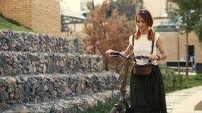 Junges redhaired Frauenreitfahrrad in der Stadt stockbilder