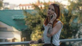 Junges redhaired Frauenreitfahrrad in der Stadt Frau mit Handy stockfoto