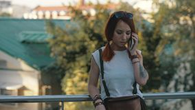 Junges redhaired Frauenreitfahrrad in der Stadt Frau mit Handy lizenzfreie stockfotos
