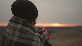Junges Reisendmädchen eingewickelt im Plaid, das mit Schale des Getränkes bei Sonnenuntergang sich entspannt Einsamkeit, Freiheit stock video footage