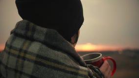 Junges Reisendmädchen eingewickelt im Plaid, das mit Schale des Getränkes bei Sonnenuntergang sich entspannt Einsamkeit, Freiheit stock video
