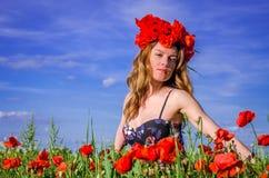 Junges reizend Mädchen geht auf das Feld mit blühenden Mohnblumen mit einem Kranz von Mohnblumen auf ihrem Kopf Stockbild
