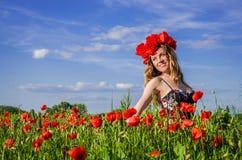 Junges reizend Mädchen geht auf das Feld mit blühenden Mohnblumen mit einem Kranz von Mohnblumen auf ihrem Kopf Lizenzfreie Stockfotografie