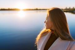 Junges reizend Mädchen mit einem herrlichen glänzenden Haar betrachtet schönen See auf einem Sonnenuntergang stockfotos