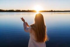 Junges reizend Mädchen mit einem herrlichen glänzenden Haar betrachtet schönen See auf einem Sonnenuntergang lizenzfreie stockbilder