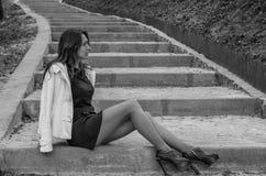 Junges reizend sexy Mädchen mit dem langen Haar in einem schwarzen Kleid schlendert in den Park auf den Schritten stockbild