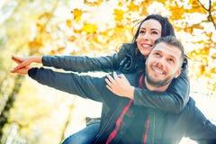 Junges reizendes glückliches Paar - die Liebhaber, die in Herbst fliegen, parken Stockfotografie