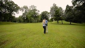Junges reizendes Paartanzen in einem Park im Sommer Romantische Datierung oder lovestory stock footage