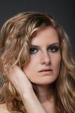Junges reizvolles blondes Frauenportrait auf Grau trennte Lizenzfreies Stockbild