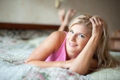Junges reizvolles playfull Mädchen auf einem Bett Lizenzfreie Stockfotografie