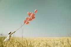 Junges romantisches Mädchen mit rotem Herzen steigt das Gehen auf einem Gebiet O im Ballon auf Lizenzfreie Stockbilder