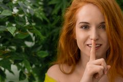 Junges Rothaarigemädchen, das bittet, Ruhe zu halten lizenzfreies stockfoto