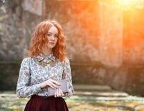 Junges rothaariges gelocktes Mädchen mit den Sommersprossen, die in einem Sommergarten mit einem Weinlesebuch in ihren Händen auf Lizenzfreies Stockbild