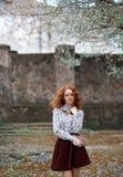 Junges rothaariges gelocktes Mädchen mit den Sommersprossen, die im Herbst im Garten mit einem Weinlesebuch in den Händen aufwerf Lizenzfreie Stockbilder