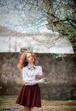 Junges rothaariges gelocktes Mädchen mit den Sommersprossen, die im Herbst im Garten mit einem Weinlesebuch in den Händen aufwerf Lizenzfreies Stockbild
