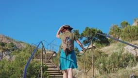 Junges rothaariges Reisendmädchen mit einem Cowboyhut und einem Rucksack klettert Treppe in einem Berggebiet stock footage