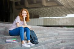 Junges Rothaarigestudentenmädchen, das draußen auf der Treppe sitzt Stockfotos