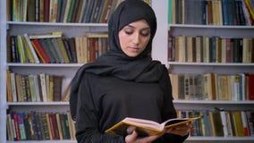 Junges süßes moslemisches Mädchen im hijab öffnet Buch, liest, religiöses Konzept, Bücherregal auf Hintergrund