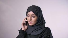Junges süßes moslemisches Mädchen im hijab spricht auf Smartphone, Kommunikationskonzept, religiöses Konzept, grauer Hintergrund