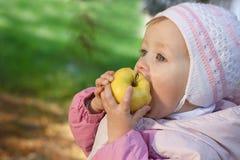 Junges Schätzchen, das einen gelben Apfel isst Lizenzfreies Stockfoto