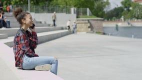 Junges schönes afroes-amerikanisch Mädchen, das am intelligenten Telefon, draußen spricht stock footage