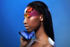 Junges schönes Afromädchen, mit zwei Schmetterlingen, Schönheitsporträt auf blauem Hintergrund Lizenzfreie Stockfotos