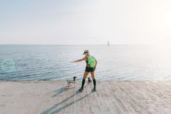 Junges schönes athletisches Mädchen mit dem langen blonden Haar in der schwarzen Kleidung und in zwei ihrer Hunde, die Sport bei  Stockbild