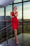 Junges schönes bezauberndes blondes Mädchen in einem roten Kleid, das nahe Glasschaukasten im Geschäftszentrum aufwirft Stockfotos