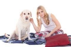 Junges schönes blondes in den Pyjamas mit dem Hund lokalisiert auf Weiß Lizenzfreies Stockbild