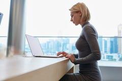Junges schönes blondes Mädchen benutzt Laptop und Telefon beim Arbeits Reise Stockfotos