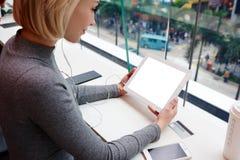 Junges schönes blondes Mädchen benutzt Laptop und Telefon beim Arbeits Reise Stockfoto