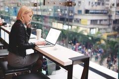 Junges schönes blondes Mädchen benutzt Laptop und Telefon beim Arbeits Schreibenmitteilungen der Reise auf Tastatur Stockfotos