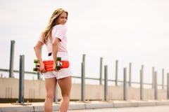 Junges schönes blondes Mädchen, das helles Skateboard auf die Brücke reitet Stockfoto