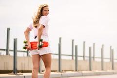 Junges schönes blondes Mädchen, das helles Skateboard auf die Brücke reitet Lizenzfreie Stockfotografie